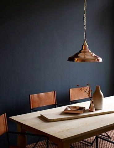 Koperen lamp op zwarte muur