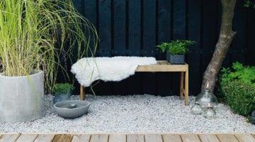Tuin met grijs grind en zwarte schutting