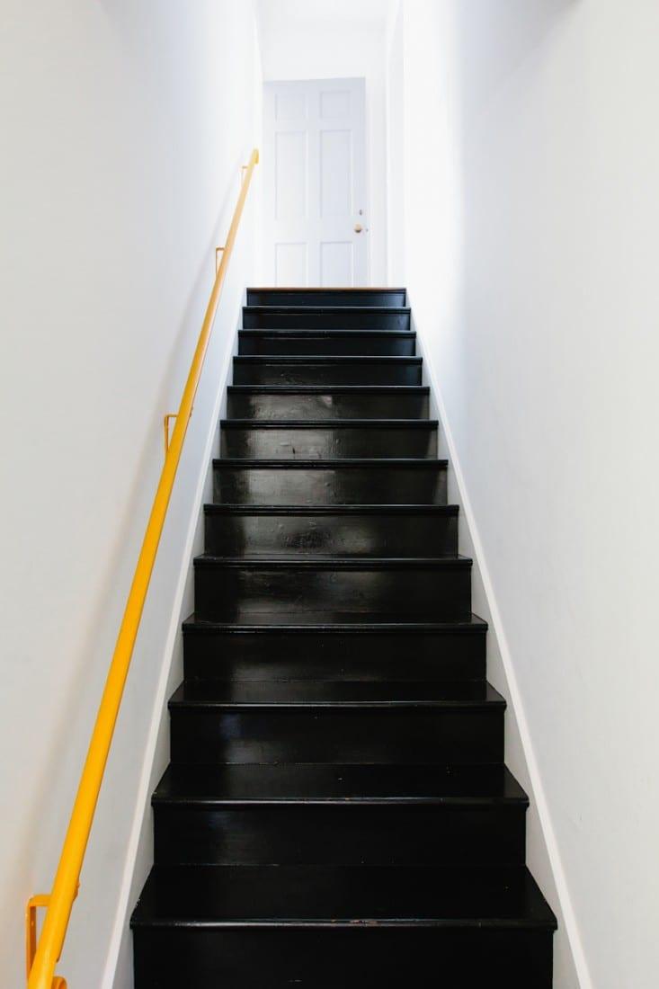 Zwarte trap met gele reling