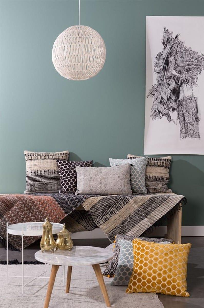 Woonkamer met blauwe muur en gele kussens