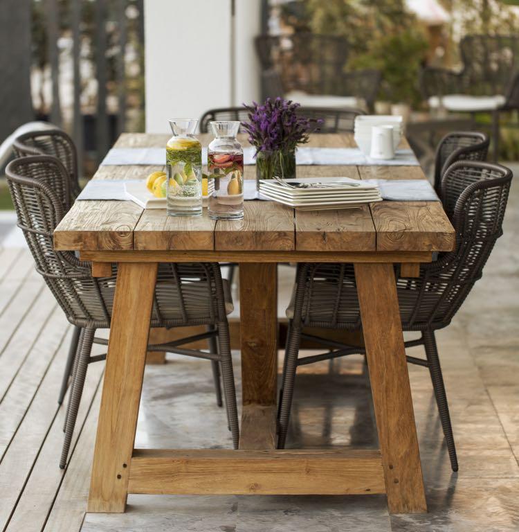 Houten tuintafel met zwarte stoelen