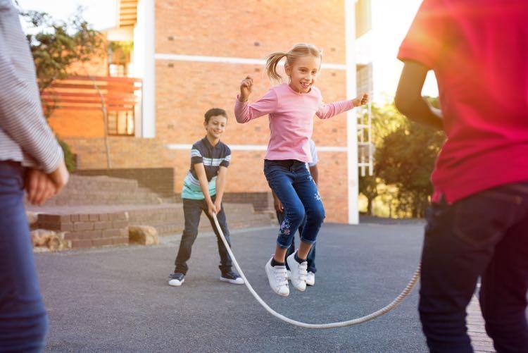 Kinderen buiten spelen op straat - springtouw